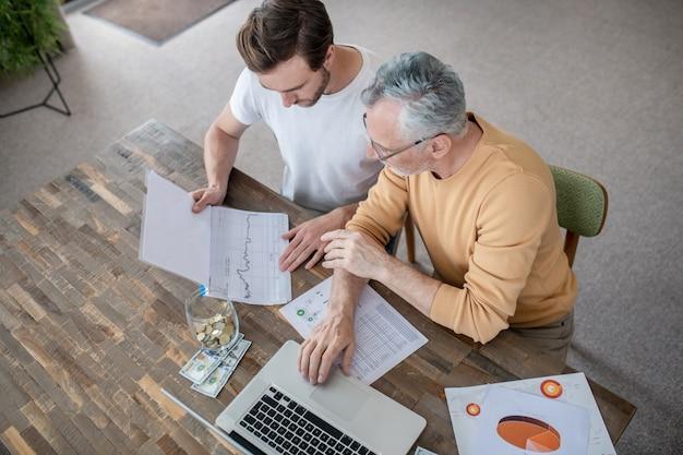 Dos hombres trabajando juntos en un proyecto y mirando concentrados