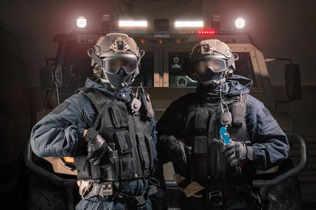 Dos hombres con uniformes militares parados en un hangar con un camión