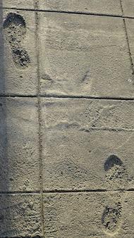 Dos huellas en la acera de cemento.