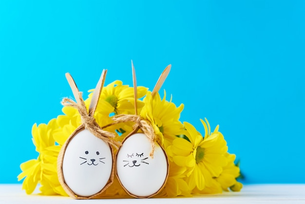 Dos huevos con caras de dibujo con flores amarillas sobre un fondo azul
