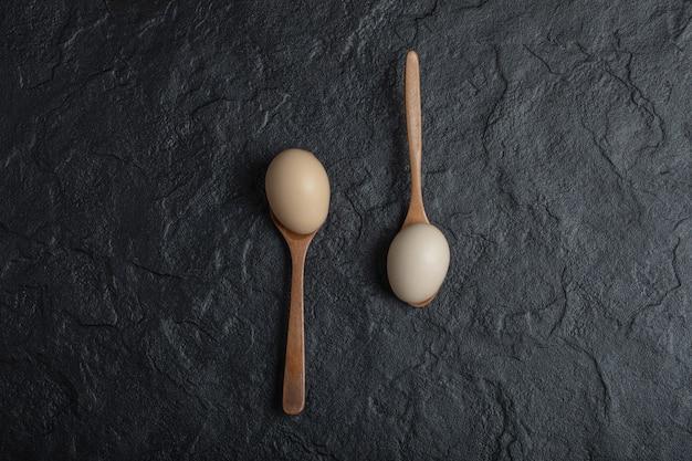 Dos huevos de gallina frescos en cucharas de madera.