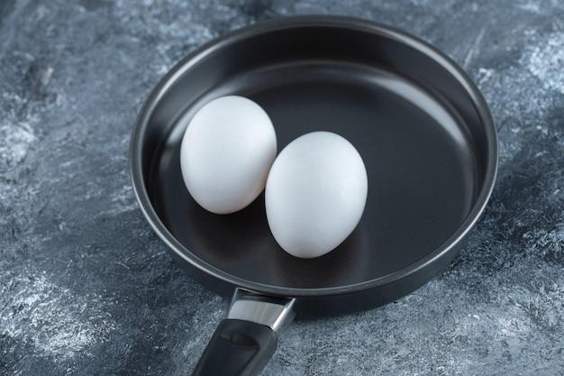 Dos huevos de gallina orgánicos en una sartén negra.