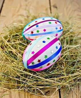Dos huevos de pascua, decorados con trenzas multicolores y destellos como asteriscos en el heno en el fondo de tablas de madera