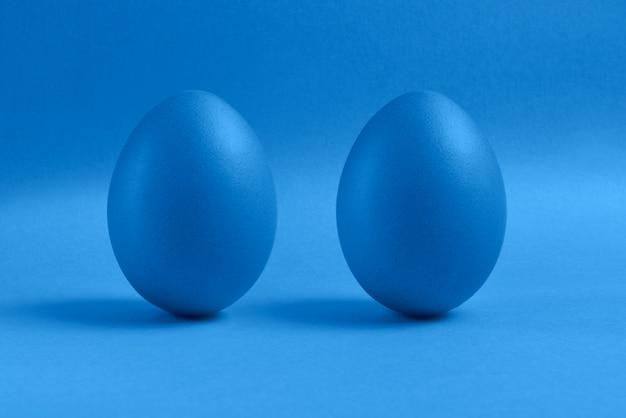 Dos huevos de pascua pintados azules se colocan en un fondo azul. feliz tarjeta de vacaciones de pascua o banner.