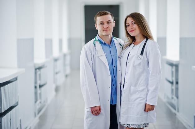 Dos impresionantes médicos o trabajadores médicos con batas blancas posan con estetoscopio en la clínica o en el hospital.