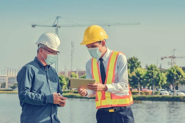 Dos ingeniero en mascarilla hablando proyecto de cepillado en la construcción del sitio