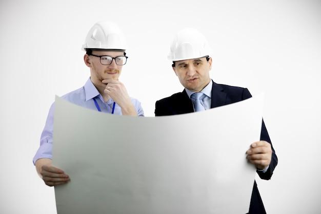 Dos ingenieros en cascos trabajando, reuniéndose, discutiendo el diseño del edificio