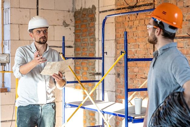 Dos ingenieros constructores hablando en el sitio de construcción, ingeniero explicando un dibujo a un trabajador.