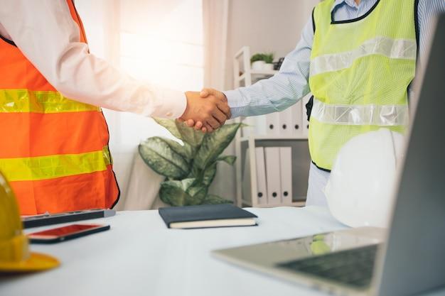 Dos ingenieros se dan la mano después de planificar