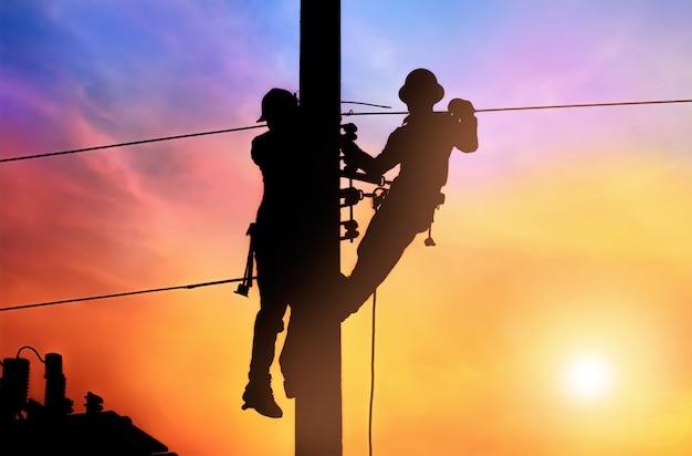 Dos ingenieros eléctricos trabajan en postes eléctricos de energía y cortes de energía de reparación
