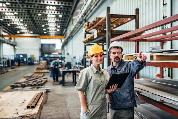 Dos ingenieros, un hombre y una mujer, discuten en la fábrica.