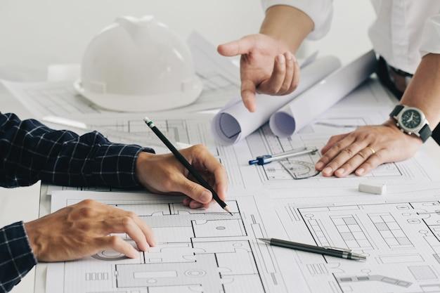 Dos ingenieros de obras de construcción de hombre de negocios trabajando en el plano y discutiendo el piso
