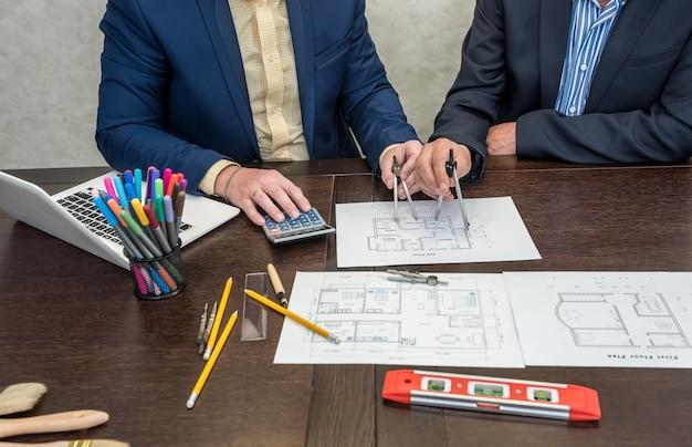 Dos ingenieros que trabajan junto con el plano de la casa de arquitectura en el escritorio de la oficina con ordenador portátil y herramientas. nuevo diseño de hogar moderno
