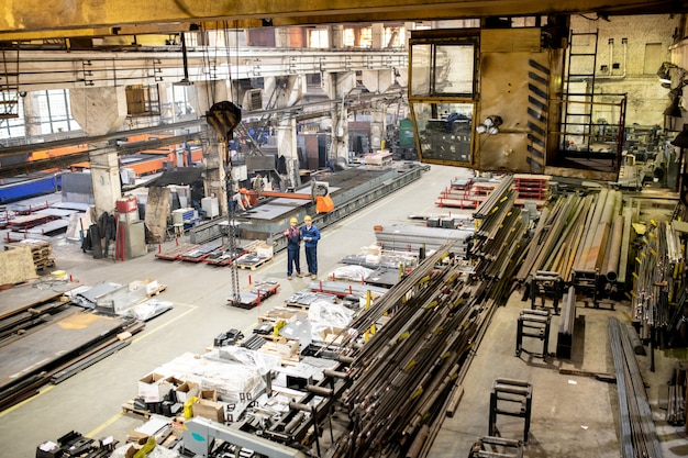 Dos ingenieros en ropa de trabajo interactuando dentro de un gran almacén industrial entre equipos nuevos