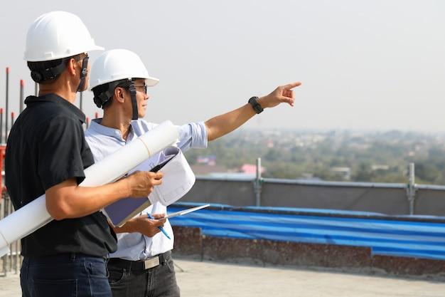 Dos ingenieros trabajan en el sitio de construcción. están comprobando el progreso del trabajo.