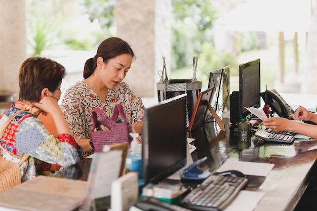 Dos invitados femeninos que revisan los documentos del hotel en la recepción