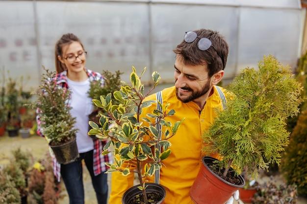 Dos jardineros sonrientes sosteniendo macetas con árboles de hoja perenne y reubicando