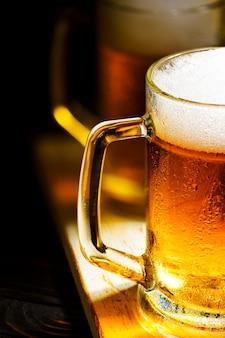 Dos jarras de cerveza ligera con espuma blanca