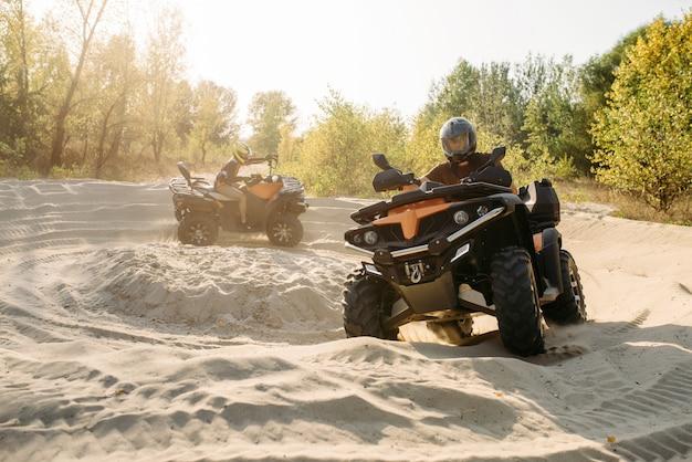 Dos jinetes de atv en cascos viajan en círculo sobre arena.
