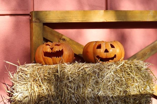 Dos jotas o linterna en un paquete de paja. calabazas de halloween. decoraciones de halloween al aire libre