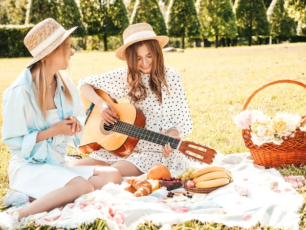 Dos joven hermosa mujer hipster en vestidos de verano de moda y sombreros. mujeres despreocupadas haciendo picnic afuera.