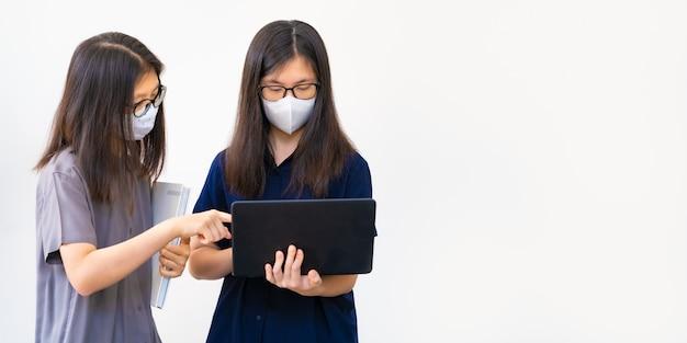 Dos jóvenes adolescentes asiáticos, con máscaras, trabajando muy juntos en su proyecto escolar