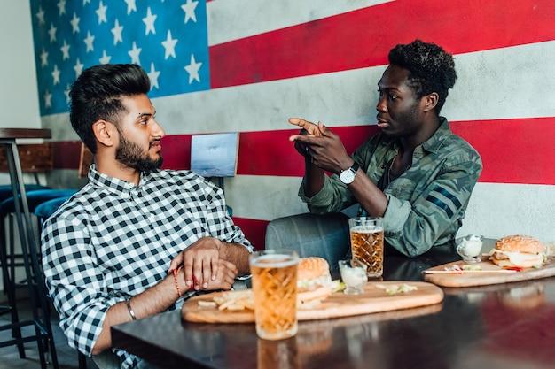 Dos jóvenes alegres bebiendo cerveza y comen hamburguesas en el bar americano moderno.