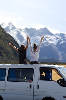 Dos jóvenes alegres se divierten levantando las manos frente al monte cook mientras se sientan en el techo de la camioneta