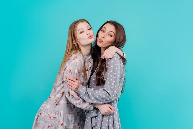 Dos jóvenes amigas abrazos y besos aislados