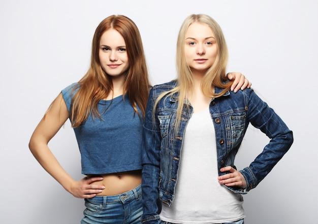 Dos jóvenes amigas de pie juntos y divertirse.