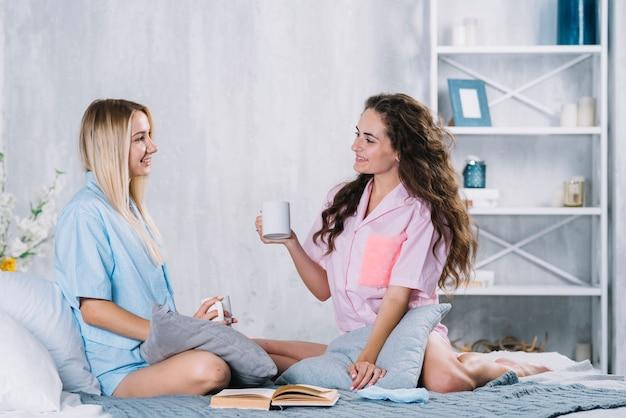 Dos jóvenes amigas sentada en la cama disfrutando de una taza de café