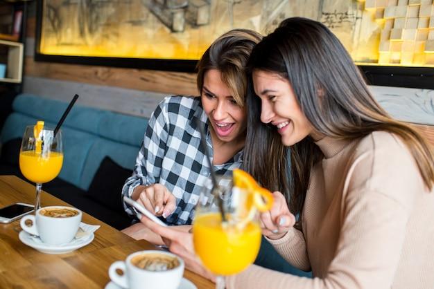 Dos jóvenes amigas sentadas en la cafetería