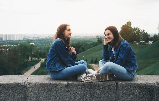Dos jóvenes amigos felices divirtiéndose en el parque de la ciudad