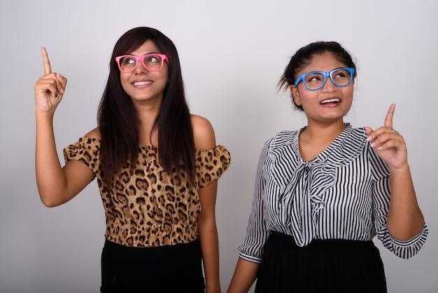 Dos jóvenes amigos felices sonriendo mientras piensan y señalan con el dedo con anteojos juntos