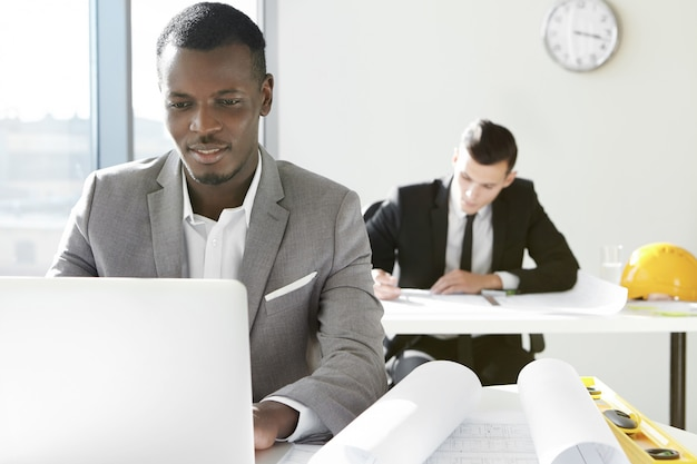 Dos jóvenes arquitectos de la empresa de ingeniería que trabajan en la oficina. diseñador africano desarrollando un nuevo proyecto de construcción usando una computadora portátil, sentado en un escritorio con rollos y regla.