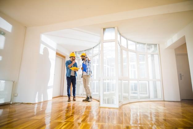 Dos jóvenes arquitectos varones caminando por un apartamento vacío hablando sobre algunos cambios.