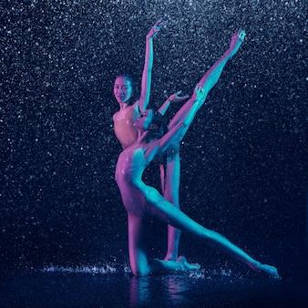 Dos jóvenes bailarinas de ballet bajo las gotas de agua