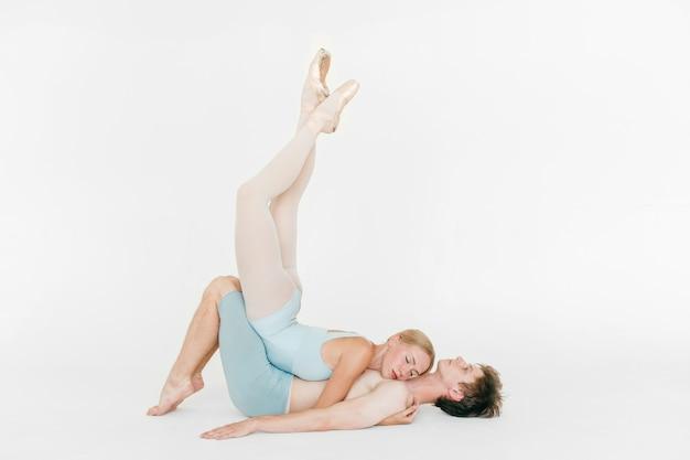 Dos jóvenes bailarines de ballet clásico practicando contra el fondo blanco de estudio