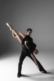 Dos jóvenes bailarines de ballet moderno en la pared gris