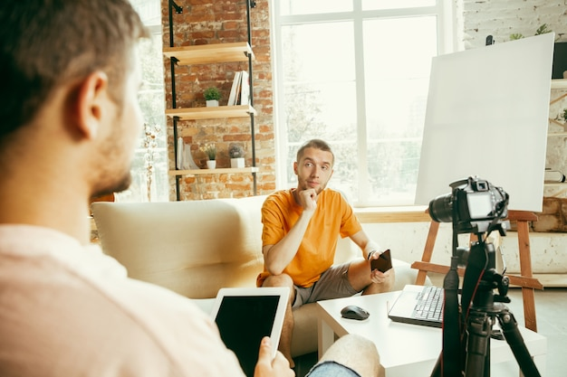 Dos jóvenes bloggers varones caucásicos en ropa casual con equipo profesional o cámara de grabación de video entrevista en casa