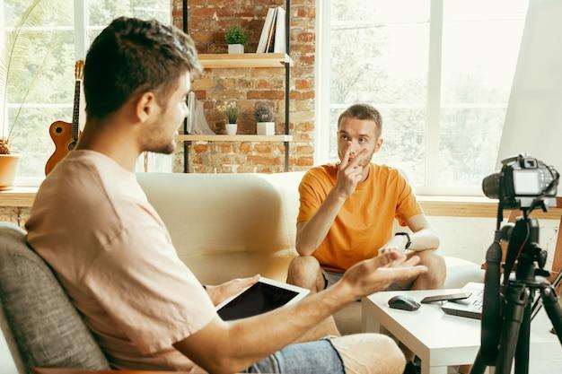 Dos jóvenes bloggers varones caucásicos en ropa casual con equipo profesional