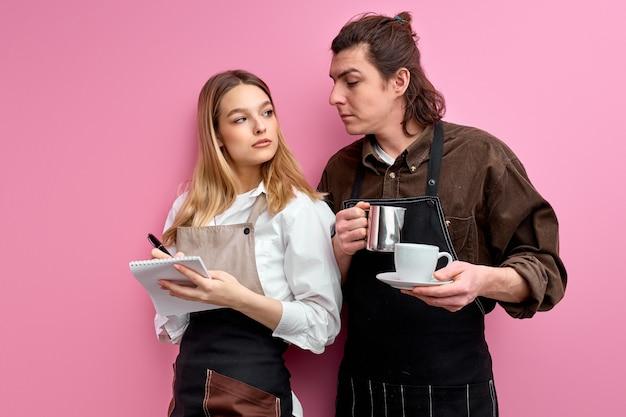 Dos jóvenes camareros en delantal discuten los pedidos, listos para servir a los clientes, una amable camarera de pie escribiendo notas