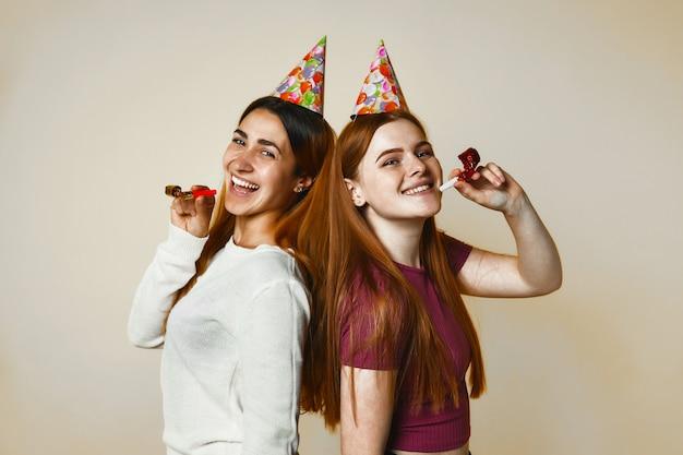 Dos jóvenes caucásicas con sombreros de cumpleaños sonríen sinceramente