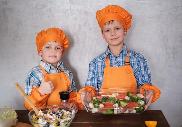 Dos jóvenes chefs con trajes anaranjados cocinan pescado rojo con brócoli y ensalada de verduras. dos hermanos de apariencia europea. cena familiar.