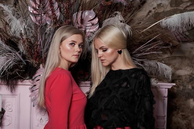 Dos jóvenes chicas sexy con elegante cabello largo y rubio y maquillaje glamoroso y de moda y vestidos rojos cerca del piano