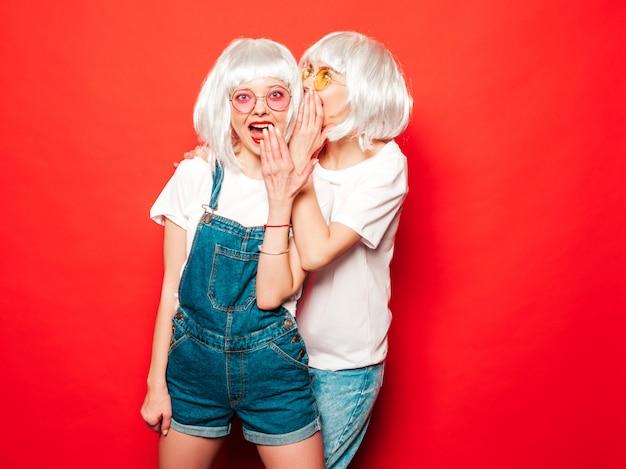 Dos jóvenes chicas sexy hipster con pelucas blancas y labios rojos. hermosas mujeres de moda en ropa de verano. modelos despreocupadas posando junto a la pared roja en verano de estudio comparte secretos, chismes