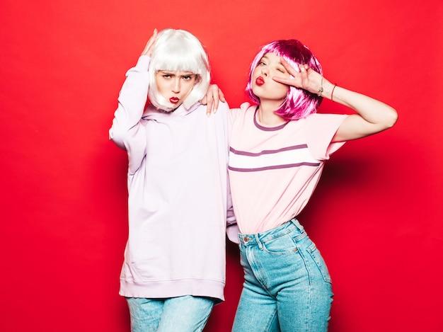 Dos jóvenes chicas sexy hipster sonrientes con pelucas blancas y labios rojos. hermosas mujeres de moda en ropa de verano. modelos despreocupados posando junto a la pared roja en el estudio volviéndose loco