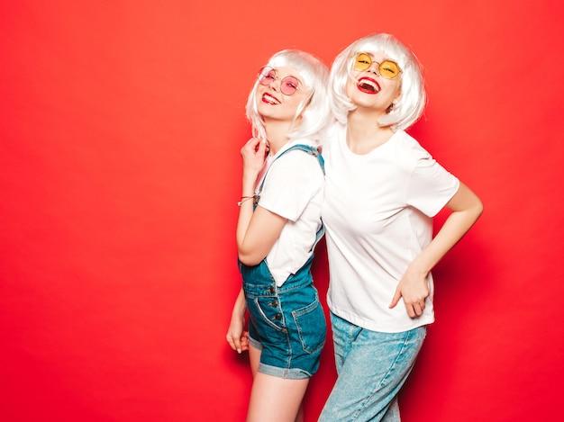 Dos jóvenes chicas sexy hipster sonrientes con pelucas blancas y labios rojos. hermosas mujeres de moda en ropa de verano. modelos despreocupados posando junto a la pared roja en verano de estudio volviéndose loco
