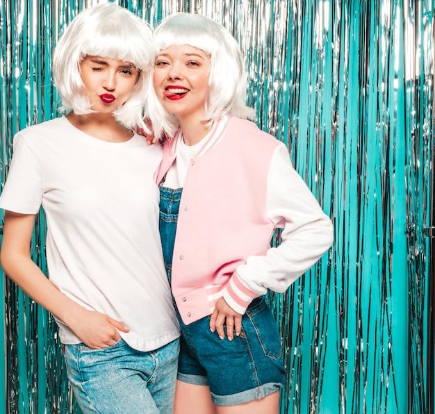 Dos jóvenes chicas sexy hipster sonrientes con pelucas blancas y labios rojos. hermosas mujeres de moda en ropa de verano verano