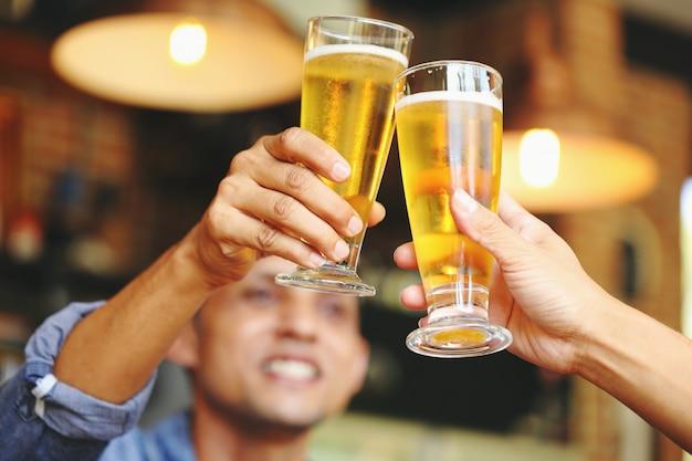 Dos jóvenes chocan con dos vasos de cerveza para celebrar su éxito.